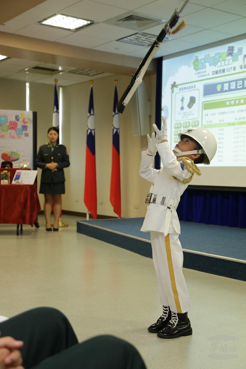 儀隊小禮兵向杰恩在記者會中操槍表演,隨後也抽出獎項。(軍聞社記者周力行攝)